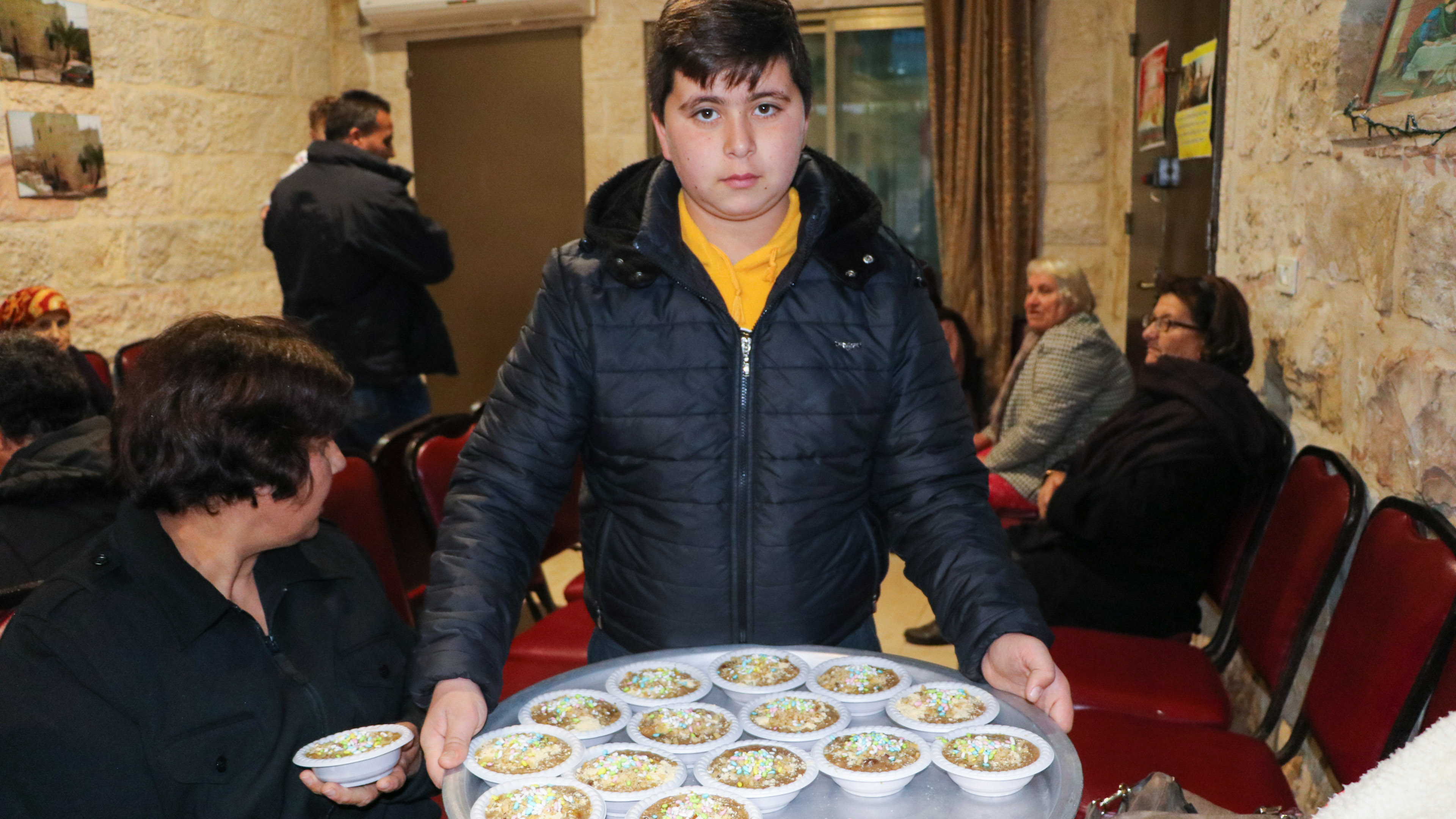 A local boy serves burburah, the traditional food of St. Barbara's Day - by Stephanie Saldaña.