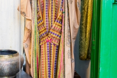 "An antique dealer displays an old palestinian dress using the multi-colored Damascene ""Joseph\"" fabric - by Aaron Cederberg"