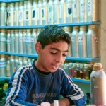 A young boy mixes perfumes. Photo by Linda Delikiz.