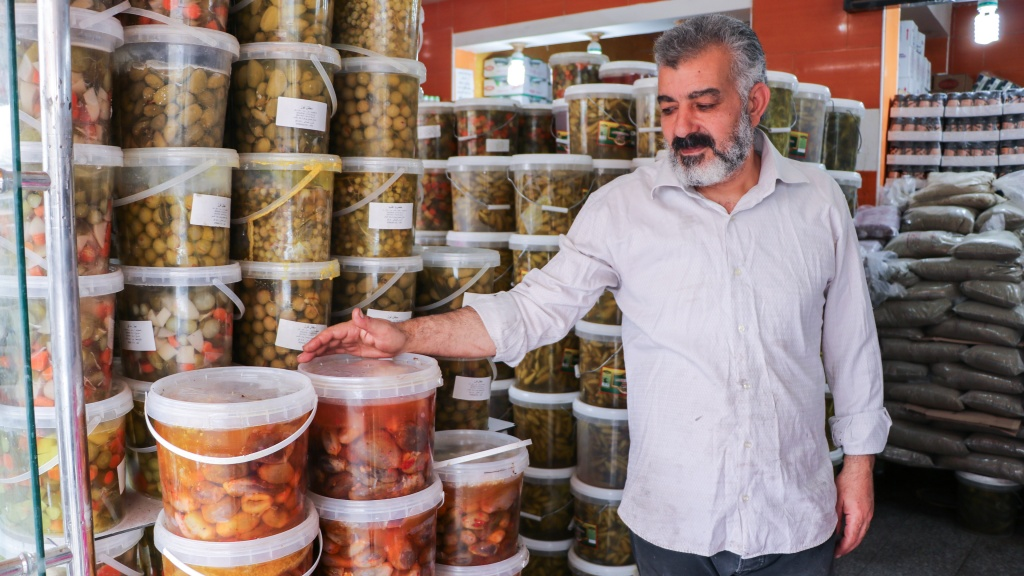 Munther, originally from Hama, sells makdous in the Syrian market in Ramtha, Jordan - by Stephanie Saldaña